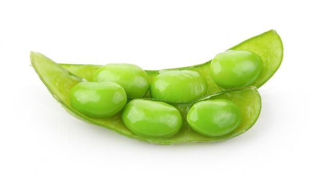 Semi di soia verde sulla tavola bianca.