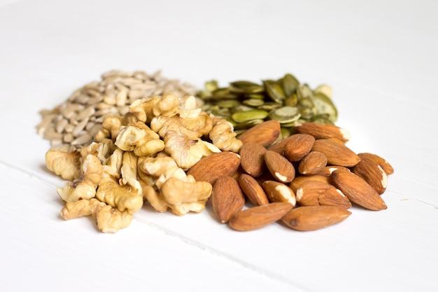 Semi di zucca, semi di girasole, mandorle, noci su legno