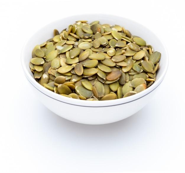 Semi di zucca (semi pelati) in una ciotola bianca (varie noci raccolta). isolato