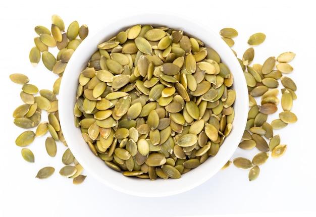 Semi di zucca (semi sbucciati) in una ciotola bianca (varie noci raccolta). isolato