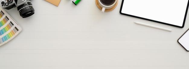 Semplice area di lavoro con tablet mock-up, tazza di caffè, altri materiali di consumo e copia spazio sulla scrivania bianca