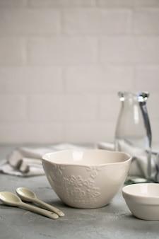 Semplice cucina domestica natura morta su una superficie di pareti chiare su un tavolo di cemento grigio. set di piatti di porcellana e bottiglia di vetro. utensile da cucina