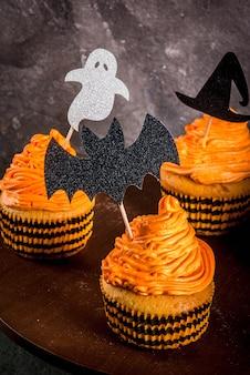 Semplice idea di scherzetto divertente per halloween: torte di zucca con panna, con decorazioni in forma di simboli di vacanze fantasma, strega, pipistrello. su un nero,