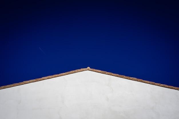 Semplice sfondo di un tetto triangolare bianco e cielo blu pulito, spazio libero per il testo