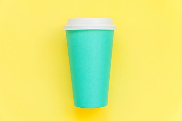 Semplicemente piatto design laici tazza di caffè in carta blu isolato su giallo colorato alla moda