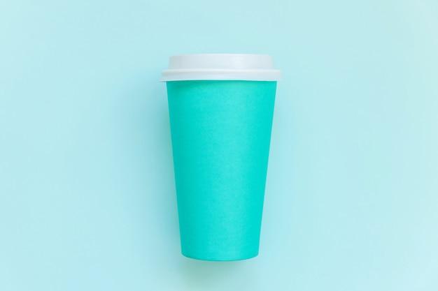 Semplicemente piatto laico design tazza di caffè in carta blu su sfondo blu pastello colorato alla moda