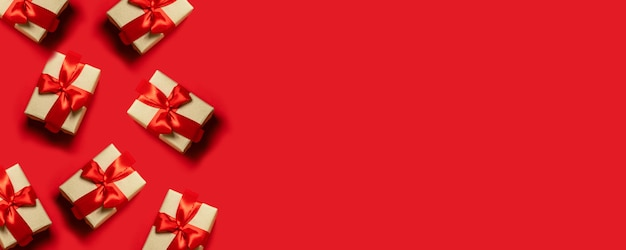 Semplici, classiche scatole regalo incartate rosse e bianche con fiocchi e decorazioni festive.