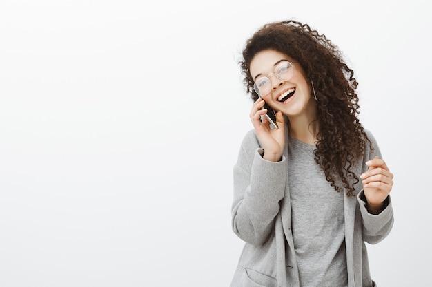 Sempre divertente parlare con te. positivo felice giovane fotografo femminile europeo in elegante cappotto e occhiali, ridendo ad alta voce