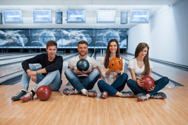 Sempre insieme. i giovani amici allegri si divertono al bowling durante i fine settimana