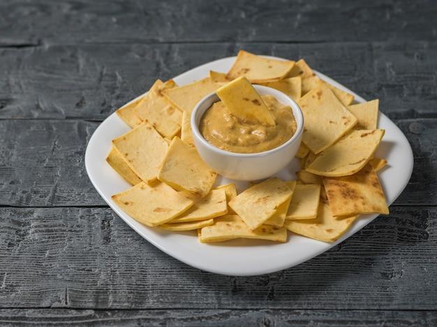 Senape con tortilla chips messicani in un piatto bianco su un tavolo di legno