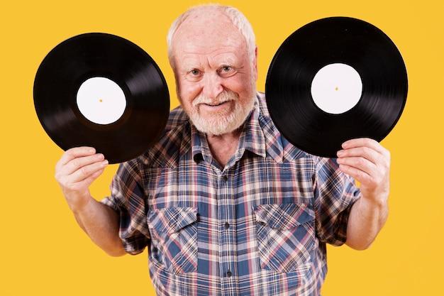 Senior ad alto angolo con due dischi musicali
