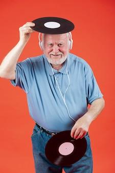 Senior dell'angolo alto che gioca con i dischi di musica