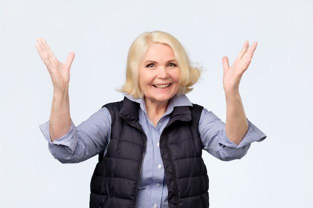 Senior donna alzando le mani per una sensazione positiva