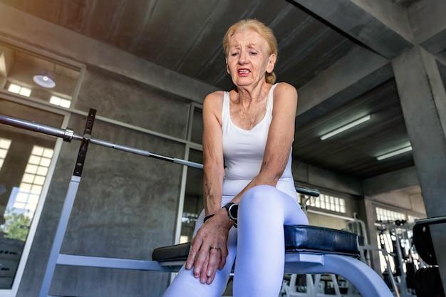 Senior donna caucasica dolore alle gambe durante l'allenamento in palestra.