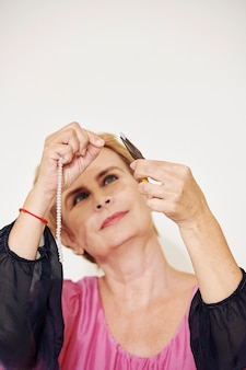 Senior donna che fa braccialetto