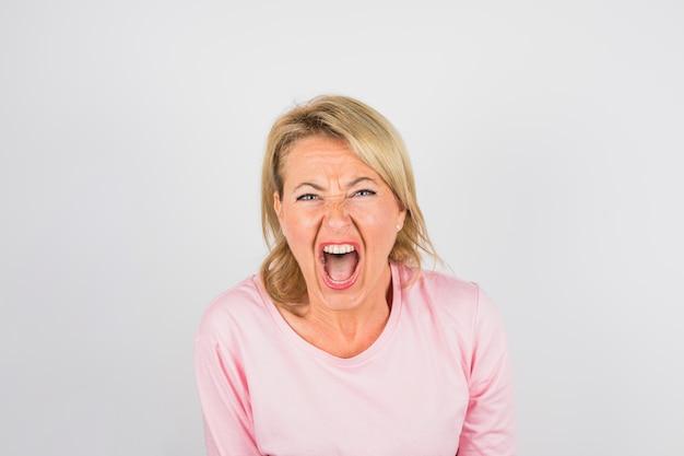 Senior donna che grida in camicetta rosa
