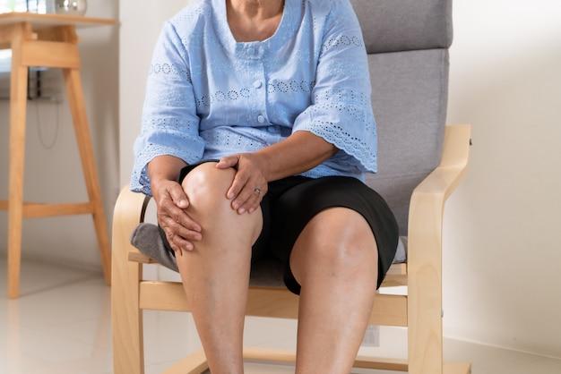 Senior donna che soffre di dolore al ginocchio a casa, concetto di problema di salute