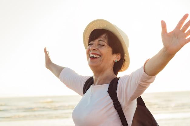 Senior donna con le braccia aperte in spiaggia. femmina più anziana che gode della libertà all'aperto in estate.