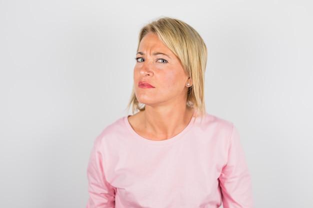 Senior donna dubbiosa in camicia rosa