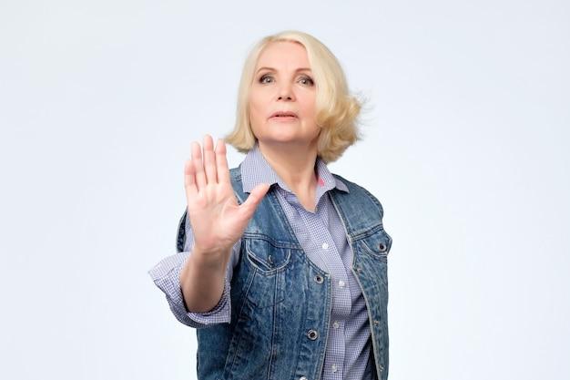 Senior donna europea che mostra il gesto di arresto