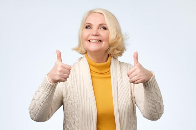 Senior donna nella sua 70s che mostra il pollice in alto gesti con entrambe le mani,