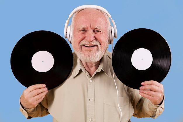 Senior maschile felice di avere dischi musicali