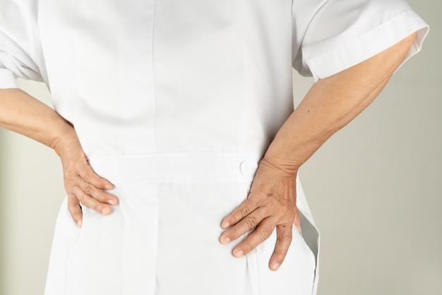 Senior medico donna che soffre di mal di schiena, toccando la schiena con la mano, dolore muscolare