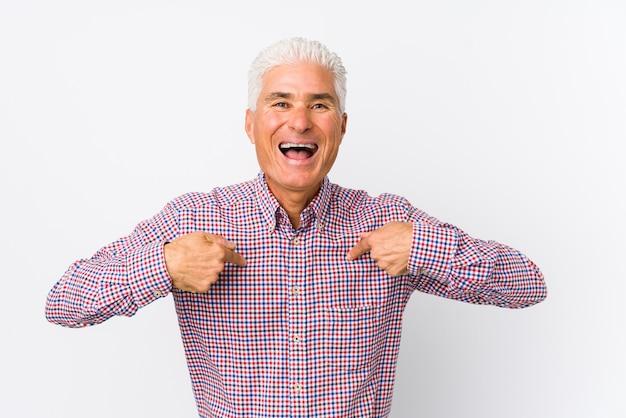 Senior uomo caucasico isolato sorpreso indicando con il dito, sorridendo ampiamente.