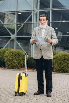 Senior uomo con la barba grigia con la valigia per il trasporto e la mappa della città sta camminando lungo l'edificio dell'aeroporto. sta guardando da parte pensieroso. copia spazio sul lato destro