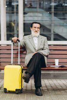 Senior uomo con la barba grigia si siede su una panchina con una valigia e una mappa della città e parla al telefono presso l'edificio dell'aeroporto