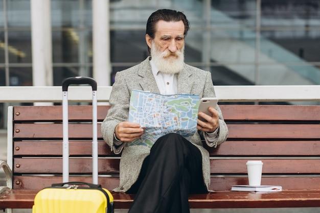 Senior uomo con la barba grigia si siede su una panchina con una valigia, guarda la mappa della città e il telefono all'edificio dell'aeroporto