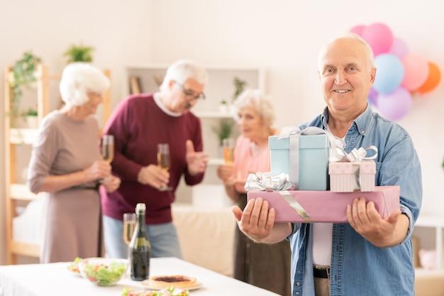 Senior uomo sorridente con diversi regali confezionati ti guarda a casa festa con gli amici