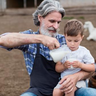 Senior versando il latte per il ragazzo carino
