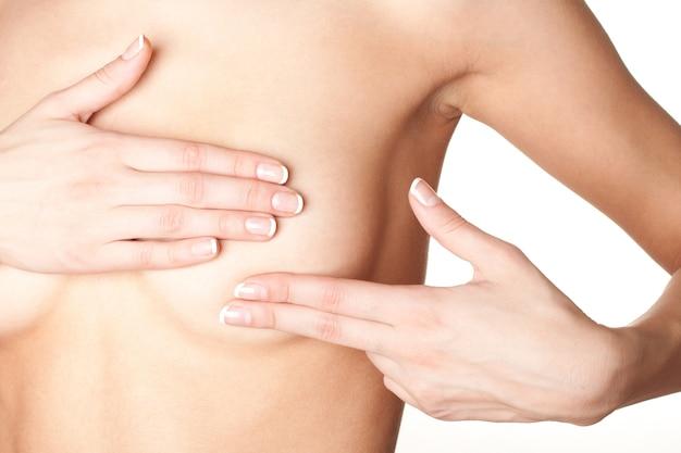 Seno di controllo femminile per cancro, isolato su superficie bianca