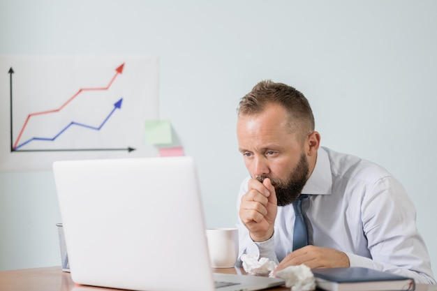 Sensazione di malessere e stanchezza. l'uomo con una tazza di tè caldo che lavora in ufficio, uomo d'affari preso freddo, influenza stagionale.