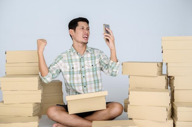 Sensazione molto soddisfatta e faccia felice dell'uomo asiatico guarda lo smartphone con alza un pugno tra tante scatole con pacchi su un muro bianco.
