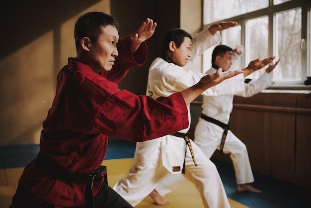 Sensei e due studenti di arti marziali fanno le posizioni insieme.
