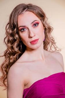 Sensuale bella ragazza bruna con trucco rosso, capelli ricci e un top bordeaux in posa su sfondo di colore limone. foto verticale