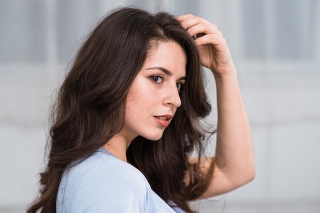 Sensuale donna accarezzando i capelli castani