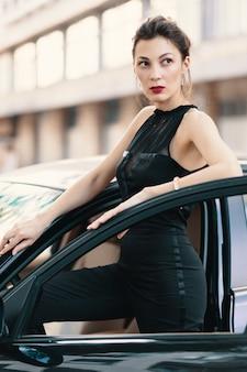 Sensuale donna pericolosa in piedi con uno sguardo felino nella portiera di un'auto pronta a vincere il mondo