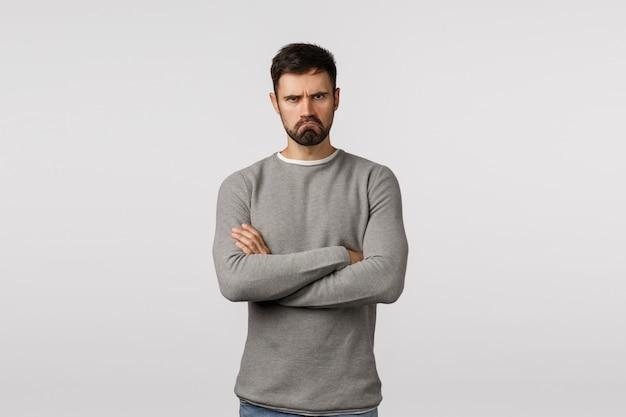 Sensuale fidanzato barbuto scontroso offeso sentirsi deluso e scontento, in piedi insultato, partner ferito i suoi sentimenti, braccia incrociate sul petto difensivo, fare espressione triste, arrabbiarsi