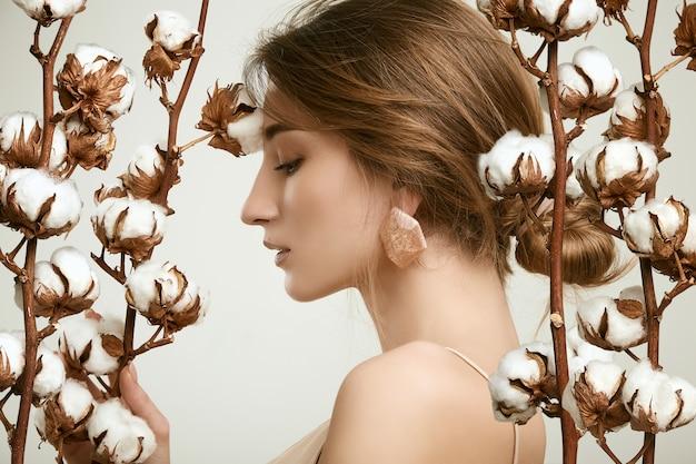 Sensuale ritratto di modello donna glamour tra rametti di cotone
