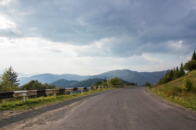 Sentiero forestale serpentino curvo della montagna in ucraino carpatico. strade principali e montagne dell'asfalto sotto il cielo blu. svuoti la strada principale della strada asfaltata nelle montagne boscose, sui precedenti un cielo nuvoloso