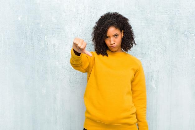 Sentirsi arrabbiati, arrabbiati, infastiditi, delusi o scontenti, mostrando il pollice giù con uno sguardo serio