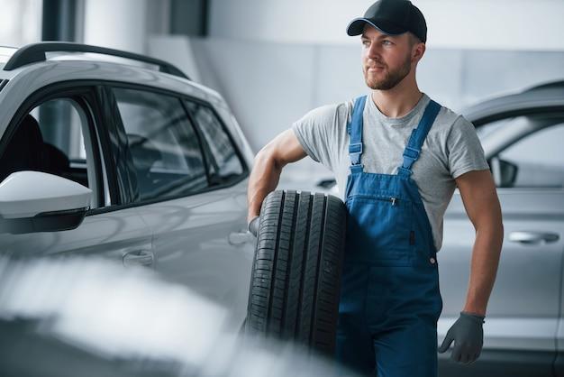 Sentirsi bene. meccanico che tiene un pneumatico al garage di riparazione. sostituzione di pneumatici invernali ed estivi
