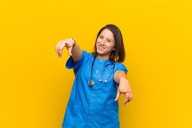 Sentirsi felici e fiduciosi, indicando la fotocamera con entrambe le mani e ridendo, scegliendo il muro giallo isolato