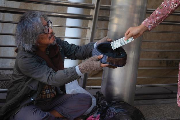 Senzatetto è seduto sulla passerella in città. sta tenendo il cappello e riceve il dollaro.