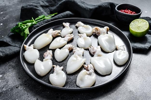 Seppie fresche con rosmarino e prezzemolo su un piatto. superficie nera. vista dall'alto