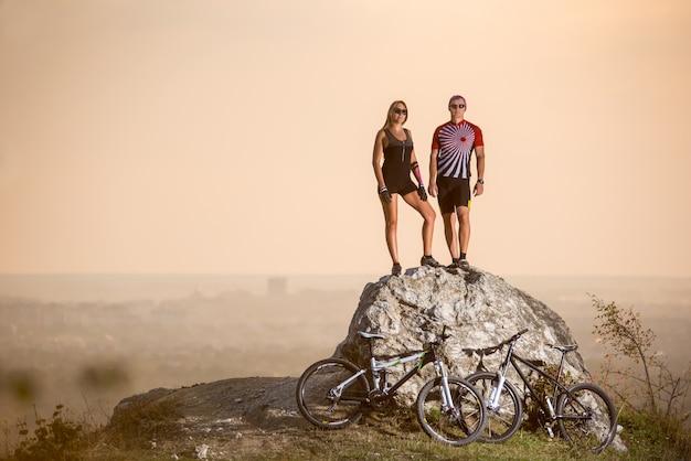 Sera d'estate i ciclisti in piedi su una grande pietra sul precipizio di una scogliera accanto a loro sono moto sportive