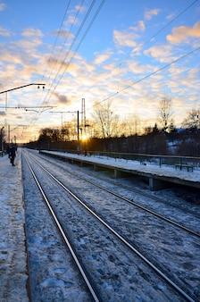 Sera paesaggio invernale con la stazione ferroviaria